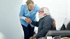 woman helping elderly man sitting