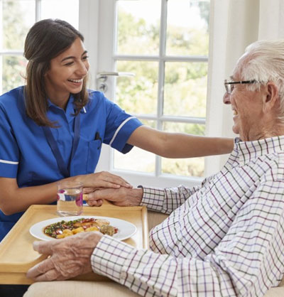 Nurse helping patient with personal care eating food