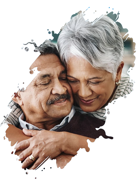Woman with light brown skin and short grey hair hugging man with light brown skin and dark grey mustache